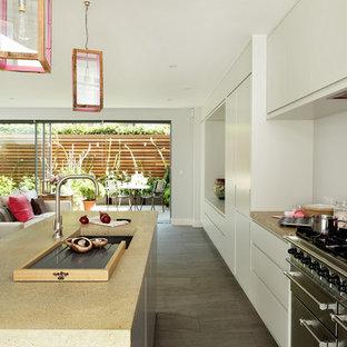 Modelo de cocina lineal, contemporánea, abierta, con armarios con paneles lisos, puertas de armario grises, encimera de cemento, salpicadero rosa, electrodomésticos con paneles, suelo de baldosas de porcelana y una isla