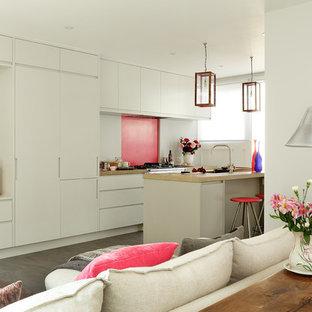 Offene, Einzeilige Moderne Küche mit flächenbündigen Schrankfronten, grauen Schränken, Betonarbeitsplatte, Küchenrückwand in Rosa, Elektrogeräten mit Frontblende, Porzellan-Bodenfliesen und Kücheninsel in London