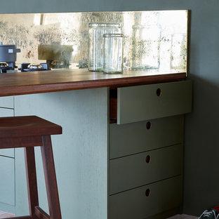 Inspiration pour une cuisine ouverte linéaire design de taille moyenne avec un évier encastré, un placard à porte plane, des portes de placards vertess, un plan de travail en marbre, une crédence métallisée, un sol en bois clair et aucun îlot.