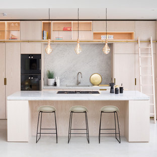 Design ideas for a contemporary galley kitchen/diner in London with a submerged sink, flat-panel cabinets, light wood cabinets, grey splashback, integrated appliances, concrete flooring, an island, grey floors and grey worktops.
