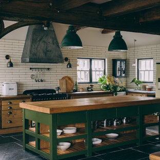 Country l-shaped kitchen in London with a farmhouse sink, open cabinets, green cabinets, wood benchtops, white splashback, subway tile splashback, with island and grey floor.