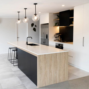 This is an example of a mid-sized scandinavian galley eat-in kitchen in Other with a double-bowl sink, flat-panel cabinets, black cabinets, solid surface benchtops, black splashback, mosaic tile splashback, stainless steel appliances, porcelain floors, with island, grey floor and white benchtop.