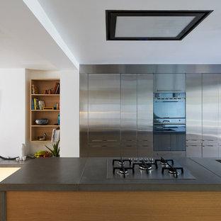 Idéer för mellanstora funkis kök, med släta luckor, skåp i rostfritt stål, bänkskiva i betong, ljust trägolv, en köksö och beiget golv