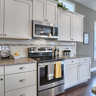 Mid-sized craftsman eat-in kitchen ideas - Example of a mid-sized arts and crafts l-shaped dark wood floor eat-in kitchen design in Other with an undermount sink, white cabinets, granite countertops, white backsplash, ceramic backsplash, stainless steel appliances, an island and shaker cabinets