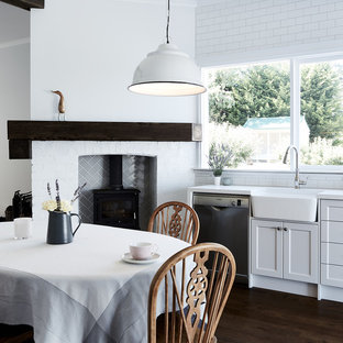 This is an example of a country single-wall eat-in kitchen in Melbourne with a farmhouse sink, shaker cabinets, white cabinets, white splashback, subway tile splashback, stainless steel appliances, dark hardwood floors and no island.