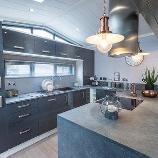 他の地域の小さいエクレクティックスタイルのおしゃれなキッチン (アンダーカウンターシンク、フラットパネル扉のキャビネット、グレーのキャビネット、コンクリートカウンター、淡色無垢フローリング、グレーのキッチンカウンター) の写真