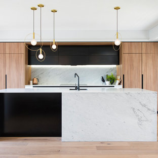 Mid-sized contemporary galley kitchen in Sydney with an undermount sink, light wood cabinets, solid surface benchtops, white splashback, marble splashback, stainless steel appliances, light hardwood floors and with island.