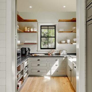 Пример оригинального дизайна: п-образная кухня в стиле кантри с кладовкой, раковиной в стиле кантри, фасадами в стиле шейкер, серыми фасадами, светлым паркетным полом, бежевым полом и серой столешницей без острова