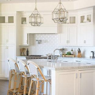 Foto de cocina costera con fregadero sobremueble, armarios estilo shaker, puertas de armario blancas, salpicadero blanco, suelo de madera oscura, una isla y suelo marrón