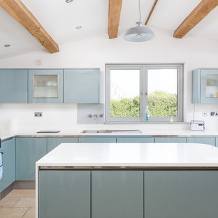 This is an example of a large traditional l-shaped kitchen/diner in Gloucestershire with flat-panel cabinets, blue cabinets, an island, beige floors, white worktops, a built-in sink and coloured appliances.