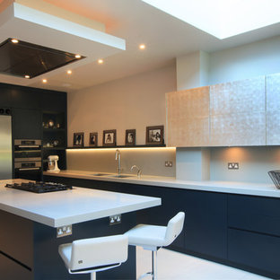 Inspiration for a medium sized contemporary l-shaped open plan kitchen in London with flat-panel cabinets, blue cabinets, quartz worktops, grey splashback, glass sheet splashback, stainless steel appliances, ceramic flooring, a breakfast bar and a submerged sink.