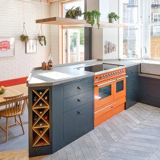 Idee per una cucina abitabile tradizionale con ante nere, top in cemento, elettrodomestici colorati, penisola, pavimento grigio e top grigio