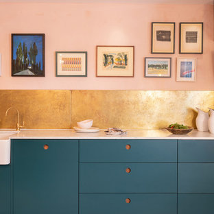 Moderne Küche mit flächenbündigen Schrankfronten, blauen Schränken und weißer Arbeitsplatte