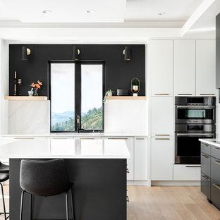 На фото: кухня в современном стиле с плоскими фасадами, черными фасадами, фартуком с окном, техникой из нержавеющей стали, светлым паркетным полом, островом, бежевым полом и белой столешницей