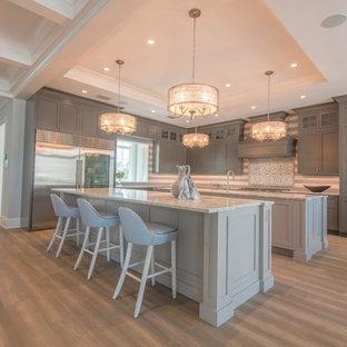 Idéer för att renovera ett mycket stort vintage grå grått kök, med en undermonterad diskho, skåp i shakerstil, grå skåp, marmorbänkskiva, grått stänkskydd, stänkskydd i mosaik, rostfria vitvaror, ljust trägolv, flera köksöar och grått golv
