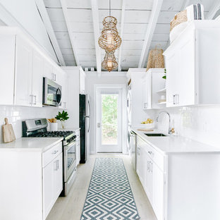 This is an example of a small nautical galley kitchen pantry in Providence with a single-bowl sink, recessed-panel cabinets, white cabinets, granite worktops, white splashback, ceramic splashback, stainless steel appliances, light hardwood flooring, no island, beige floors and white worktops.