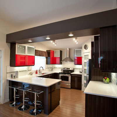 Example of a trendy u-shaped kitchen design in Calgary with red cabinets, flat-panel cabinets and stainless steel appliances
