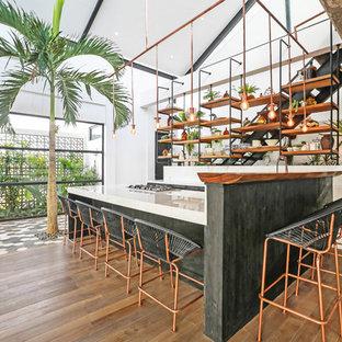 Aménagement d'une cuisine exotique en U avec des portes de placard noires, une crédence blanche, une péninsule, un sol marron et un plan de travail blanc.