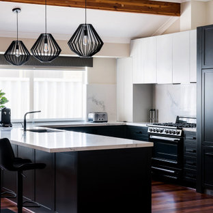 Design ideas for a transitional u-shaped kitchen in Perth with an undermount sink, shaker cabinets, black cabinets, white splashback, stone slab splashback, black appliances, dark hardwood floors, a peninsula, brown floor, white benchtop and vaulted.