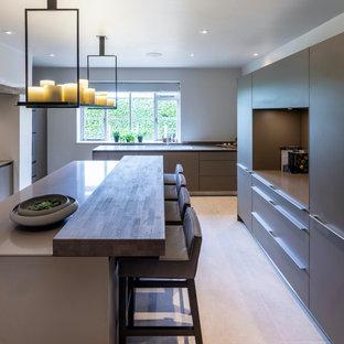 チェシャーの広いコンテンポラリースタイルのおしゃれなキッチン (エプロンフロントシンク、フラットパネル扉のキャビネット、グレーのキャビネット、クオーツストーンカウンター、白いキッチンパネル、レンガのキッチンパネル、シルバーの調理設備、セラミックタイルの床、白い床、グレーのキッチンカウンター) の写真