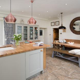 Design ideas for a medium sized rural single-wall kitchen/diner in Other with a belfast sink, shaker cabinets, grey cabinets, wood worktops, blue splashback, ceramic splashback, black appliances, ceramic flooring, an island and beige floors.