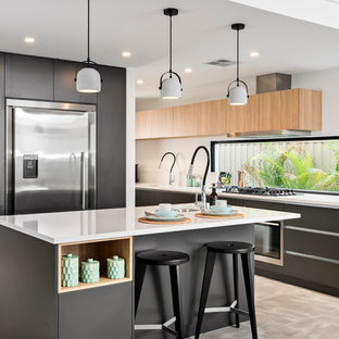 Inspiration for a mid-sized contemporary l-shaped open plan kitchen in Perth with a drop-in sink, flat-panel cabinets, black cabinets, quartz benchtops, stainless steel appliances, porcelain floors, with island, glass sheet splashback and grey floor.