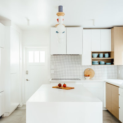 Inspiration for a mid-sized scandinavian l-shaped gray floor and concrete floor kitchen remodel in Salt Lake City with flat-panel cabinets, white cabinets, white backsplash, an island, white countertops, a single-bowl sink, mosaic tile backsplash and paneled appliances