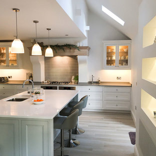 Inspiration for a large country single-wall open plan kitchen in Other with an undermount sink, beaded inset cabinets, white cabinets, granite benchtops, grey splashback, ceramic splashback, black appliances, vinyl floors and with island.