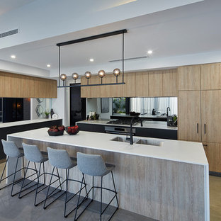 Photo of a contemporary l-shaped kitchen in Perth with a double-bowl sink, flat-panel cabinets, light wood cabinets, mirror splashback, black appliances, with island, beige floor and white benchtop.