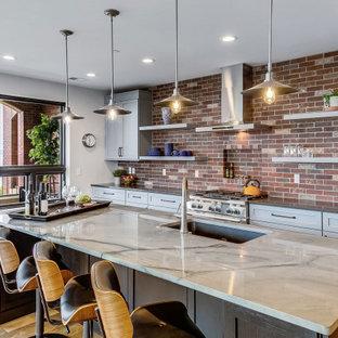他の地域のトランジショナルスタイルのおしゃれなII型キッチン (アンダーカウンターシンク、シェーカースタイル扉のキャビネット、グレーのキャビネット、マルチカラーのキッチンパネル、レンガのキッチンパネル、パネルと同色の調理設備、無垢フローリング、茶色い床、グレーのキッチンカウンター) の写真