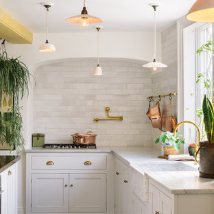 Design ideas for a large shabby-chic style eat-in kitchen in Other with a farmhouse sink, shaker cabinets, white cabinets, marble benchtops, white splashback, subway tile splashback, panelled appliances, terra-cotta floors, with island and brown floor.