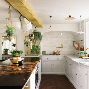 Идея дизайна: кухня в стиле шебби-шик с обеденным столом, раковиной в стиле кантри, фасадами в стиле шейкер, белыми фасадами, мраморной столешницей, белым фартуком, фартуком из плитки кабанчик, техникой под мебельный фасад, полом из терракотовой плитки, островом и коричневым полом