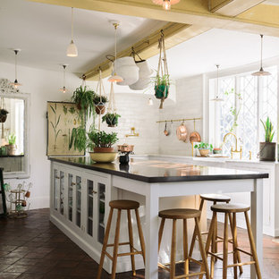Design ideas for a large country kitchen in Other with a farmhouse sink, white cabinets, marble benchtops, white splashback, subway tile splashback, terra-cotta floors, with island, brown floor, glass-front cabinets and black benchtop.