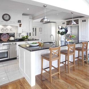 Imagen de cocina actual con electrodomésticos de acero inoxidable y suelo blanco