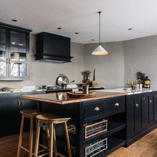 Offene, Einzeilige, Mittelgroße Country Küche mit integriertem Waschbecken, Schrankfronten im Shaker-Stil, schwarzen Schränken, Kupfer-Arbeitsplatte, Küchenrückwand in Grau, schwarzen Elektrogeräten, braunem Holzboden und Kücheninsel in Sonstige