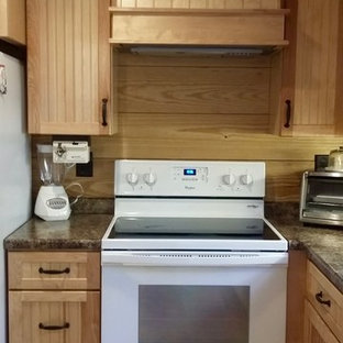 Photo of a large country u-shaped eat-in kitchen in Other with a drop-in sink, louvered cabinets, light wood cabinets, glass benchtops, brown splashback, timber splashback, white appliances, porcelain floors, brown floor and with island.
