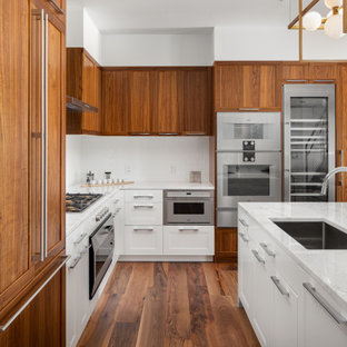 Inspiration pour une cuisine ouverte traditionnelle en L avec un évier encastré, un placard à porte shaker, des portes de placard en bois brun, une crédence blanche, un électroménager encastrable, un sol en bois brun, un îlot central, un sol marron et un plan de travail multicolore.