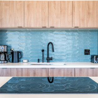 他の地域の中くらいのコンテンポラリースタイルのおしゃれなキッチン (アンダーカウンターシンク、フラットパネル扉のキャビネット、中間色木目調キャビネット、人工大理石カウンター、青いキッチンパネル、セラミックタイルのキッチンパネル、シルバーの調理設備、磁器タイルの床、ベージュの床、白いキッチンカウンター) の写真