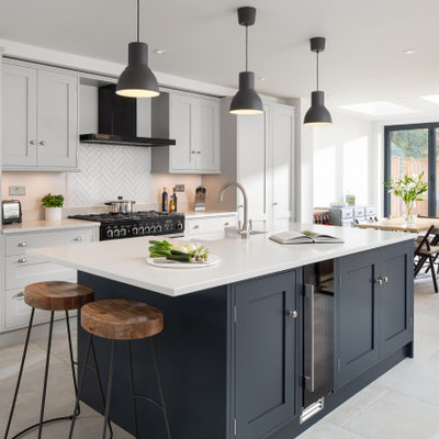 Transitional single-wall open concept kitchen photo in London with a farmhouse sink, shaker cabinets, gray cabinets, quartzite countertops, gray backsplash, subway tile backsplash, black appliances, an island and white countertops