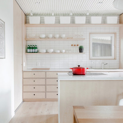 Small danish galley light wood floor and beige floor open concept kitchen photo in Calgary with an undermount sink, flat-panel cabinets, light wood cabinets, quartz countertops, white backsplash, ceramic backsplash, stainless steel appliances, an island and white countertops