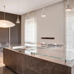 Modelo de cocina comedor contemporánea, grande, con armarios con paneles lisos, puertas de armario marrones, suelo de madera clara, una isla y encimera de vidrio