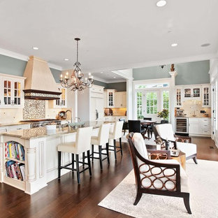 Traditional open concept kitchen pictures - Example of a classic dark wood floor and brown floor open concept kitchen design in Seattle with glass-front cabinets, beige cabinets, multicolored backsplash, stainless steel appliances, an island and beige countertops