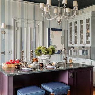 Inredning av ett klassiskt avskilt, litet kök, med en undermonterad diskho, lila skåp, bänkskiva i täljsten, rostfria vitvaror, mellanmörkt trägolv, en köksö, brunt golv och skåp i shakerstil