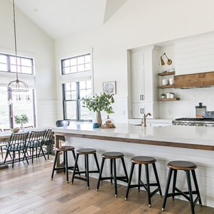 Design ideas for a medium sized country l-shaped kitchen/diner in Salt Lake City with white splashback, stainless steel appliances, medium hardwood flooring, an island, a belfast sink, shaker cabinets, white cabinets, engineered stone countertops, metro tiled splashback, brown floors and white worktops.