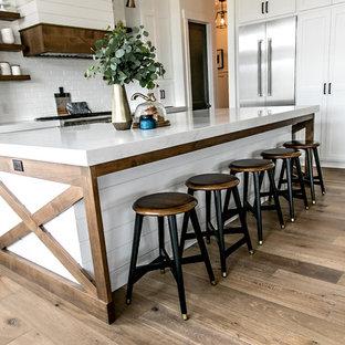 ソルトレイクシティの中サイズのカントリー風おしゃれなキッチン (エプロンフロントシンク、シェーカースタイル扉のキャビネット、白いキャビネット、クオーツストーンカウンター、白いキッチンパネル、サブウェイタイルのキッチンパネル、シルバーの調理設備、無垢フローリング、茶色い床、白いキッチンカウンター) の写真