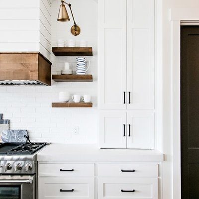 Mid-sized farmhouse medium tone wood floor and brown floor kitchen photo in Salt Lake City with a farmhouse sink, shaker cabinets, white cabinets, quartz countertops, white backsplash, subway tile backsplash, stainless steel appliances, an island and white countertops