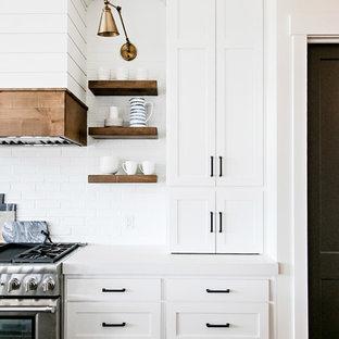 Idéer för mellanstora lantliga vitt kök, med en rustik diskho, skåp i shakerstil, vita skåp, bänkskiva i kvarts, vitt stänkskydd, stänkskydd i tunnelbanekakel, rostfria vitvaror, mellanmörkt trägolv, en köksö och brunt golv
