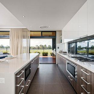 パースの広いモダンスタイルのおしゃれなキッチン (ダブルシンク、フラットパネル扉のキャビネット、中間色木目調キャビネット、珪岩カウンター、ガラス板のキッチンパネル、シルバーの調理設備) の写真