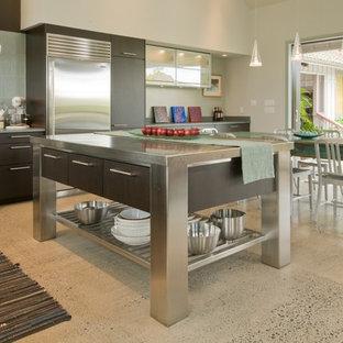 Tropische Wohnküche mit flächenbündigen Schrankfronten, Küchengeräten aus Edelstahl, Edelstahl-Arbeitsplatte und dunklen Holzschränken in Hawaii