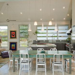 Imagen de cocina en L, tropical, abierta, con electrodomésticos de acero inoxidable, armarios con paneles lisos y puertas de armario de madera en tonos medios